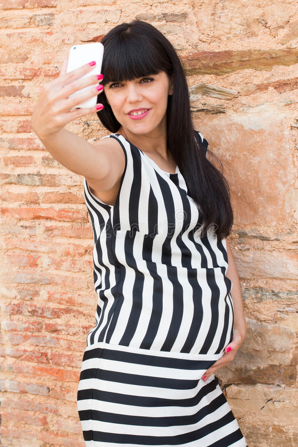 Beautiful pregnant woman making a selfie with mobile stock images