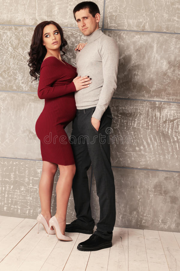 Beautiful pregnant woman posing with handsome man. Fashion studio photo of tender couple. beautiful pregnant women posing with handsome man royalty free stock images