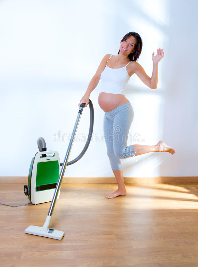 Beautiful pregnant woman retro vacuum housewife stock photography