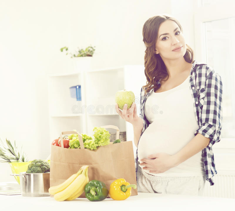 Beautiful pregnant woman with shopping bags in kitchen. Motherhood, pregnancy, maternity concept. stock photography