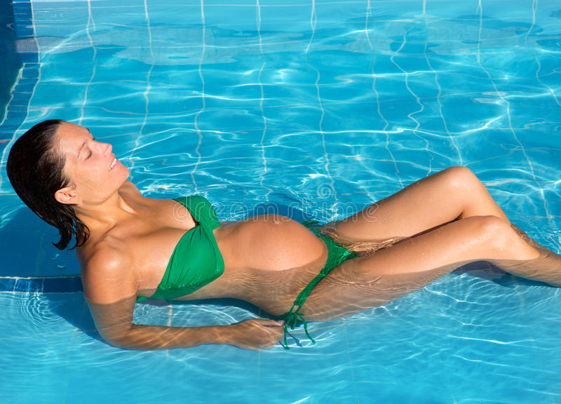 Beautiful pregnant woman sun tanning at blue pool royalty free stock images