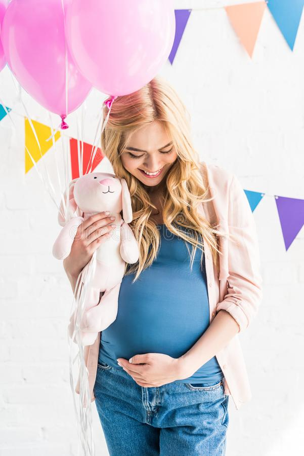 Beautiful pregnant woman touching belly and holding rabbit toy. At baby-party stock image