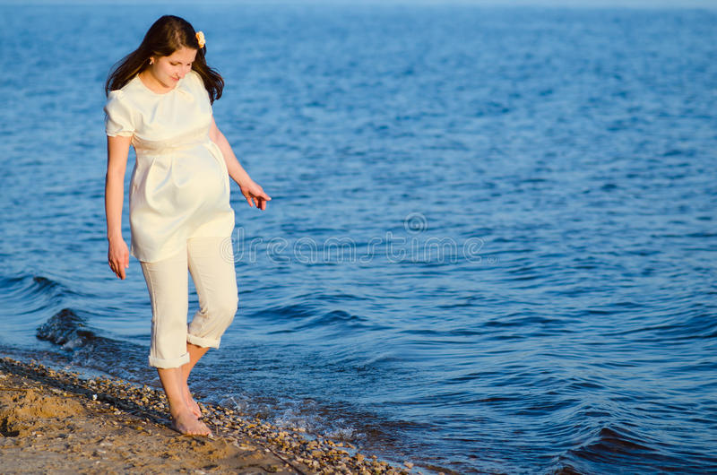 Beautiful pregnant woman walks along the shore royalty free stock photos