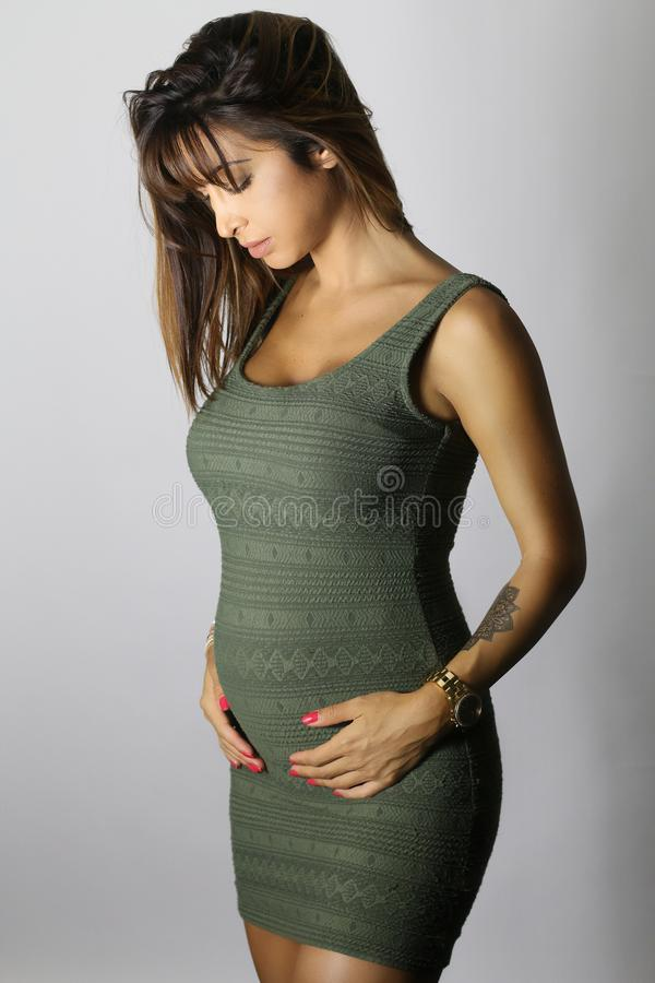 Beautiful pregnant woman wearing a green dress royalty free stock images