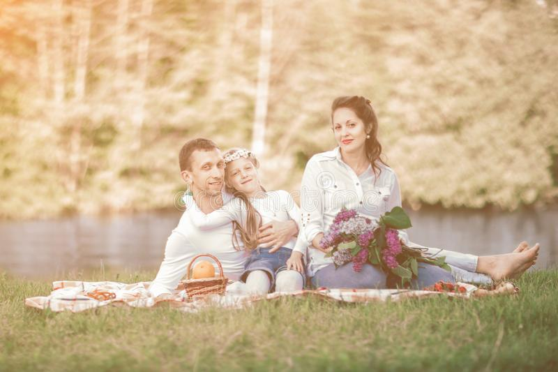 Pregnant woman with a bouquet of lilacs and her family sitting on the grass near the river royalty free stock photography