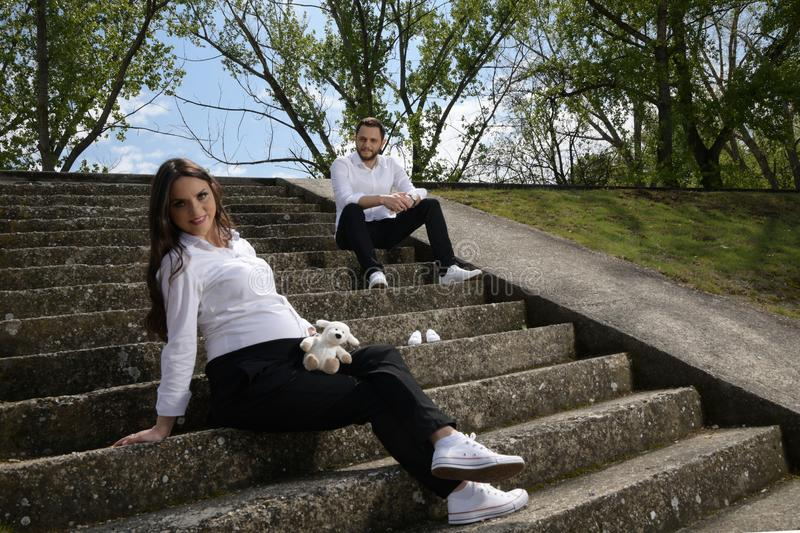 Beautiful pregnant woman and her husband sitting on a stone stairs royalty free stock image