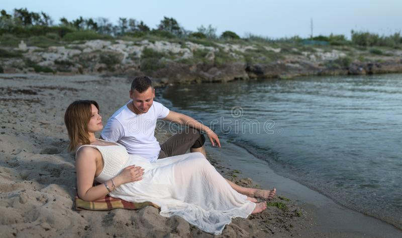 Beautiful pregnant woman and her man  sitting on the seashore royalty free stock photography