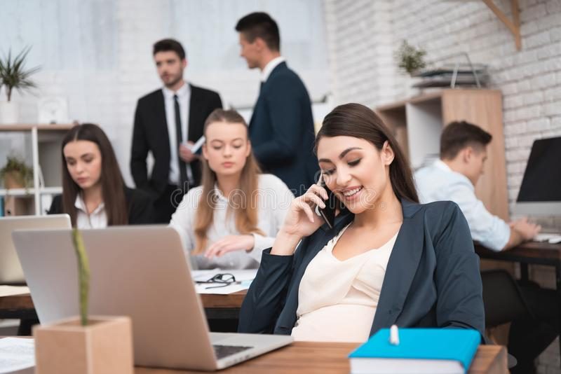Beautiful pregnant woman speaks by phone in the office. Pregnancy at work. stock image