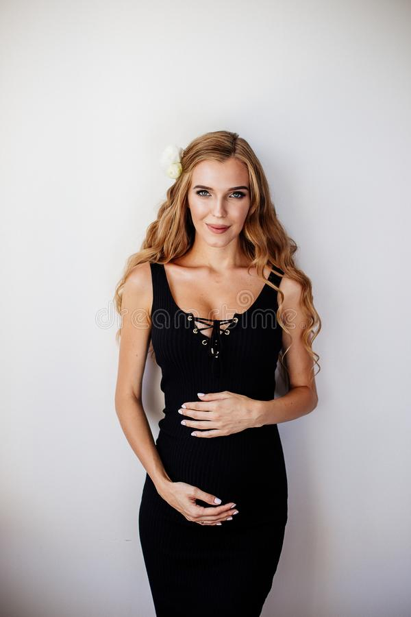 Beautiful pregnant young woman. Beautiful pregnant young woman is wearing black dress at home royalty free stock photos