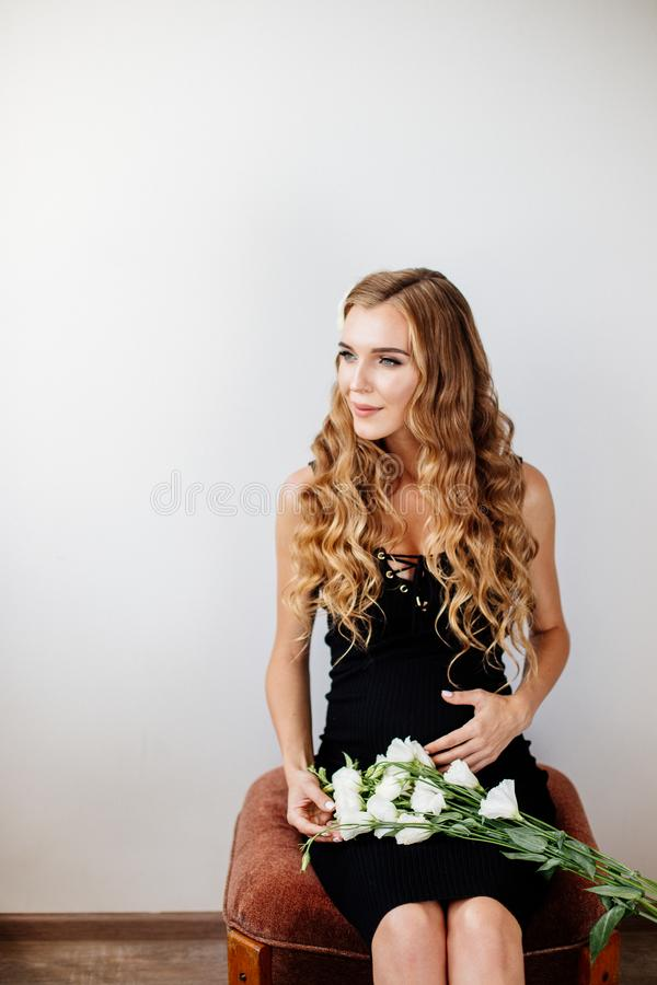 Beautiful pregnant young woman. Beautiful pregnant young woman is wearing black dress at home royalty free stock image