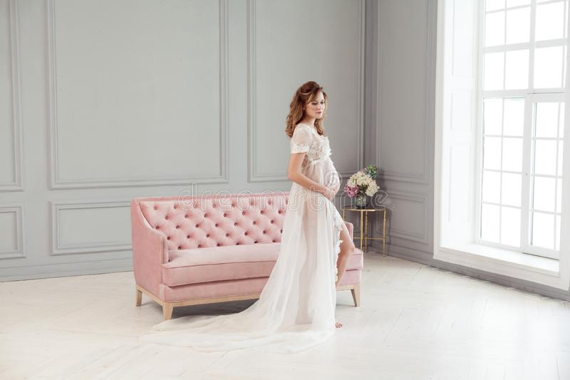 Beautiful pregnant young woman in white dress peignoir standing near pink sofa, holding with love her belly stock photo