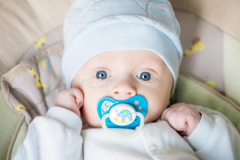 Beautiful pretty blue eyed baby kid with pacifier  on the bad and looking at the camera at home stock photography