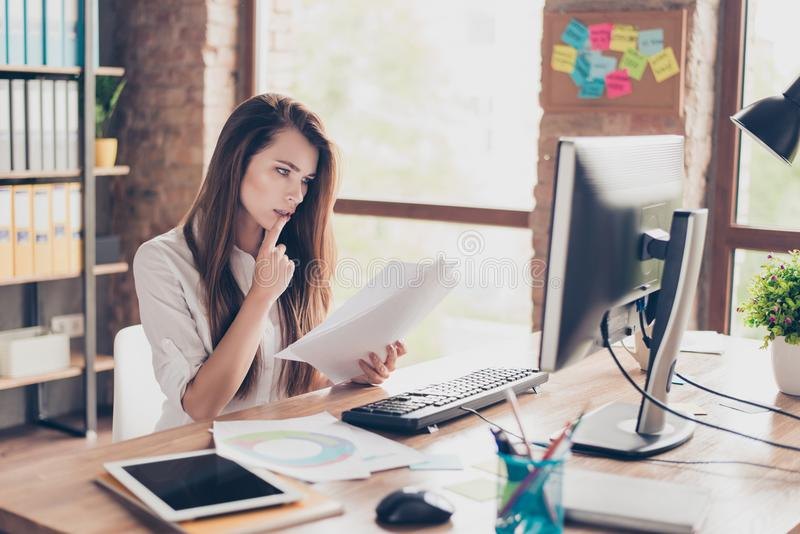 Beautiful pretty charming cute with modern hairstyle agent secretary trainee checking documents in hand looking at the monitor si. Tting at the table in light royalty free stock photo