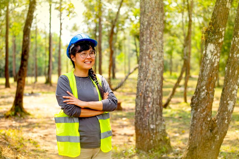 Beautiful and pretty engineer woman show action of confidence and smile with background of nature and forest in day light.  stock photography