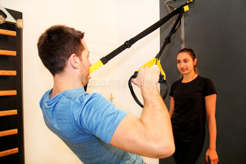 Woman with trainer exercising with a resistance band royalty free stock photography