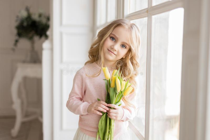 Beautiful pretty girl with yellow flowers tulips standing near big window, smiling. Indoor photo. Spring theme. Close-up. Nice royalty free stock photos