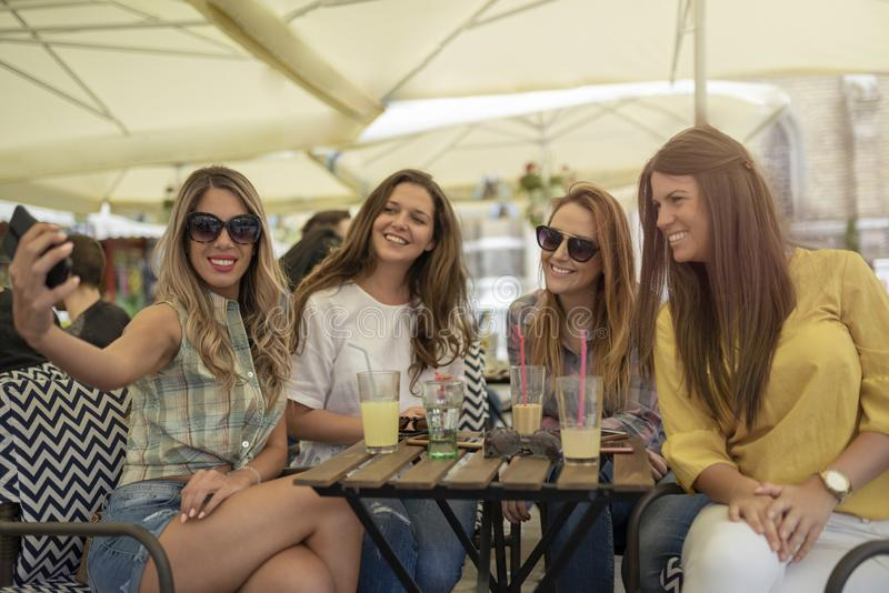 Beautiful and pretty girls having fun in cafe. Girls taking self royalty free stock images
