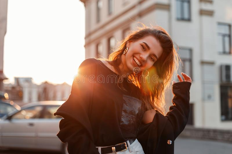 Beautiful pretty positive young woman in a stylish T-shirt in white jeans stands and laughs near vintage buildings. On a background of bright orange spring royalty free stock photo