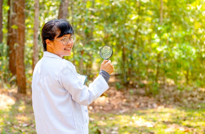 Beautiful and pretty scientist woman hold the magnifying glass and face back to right direction with the forest as background in. The concept of research or royalty free stock images