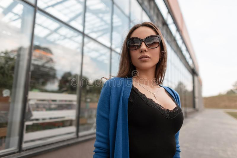 Beautiful pretty sexy young hipster woman in stylish sunglasses in a knitted cape in a T-shirt with lace is standing outdoors stock images