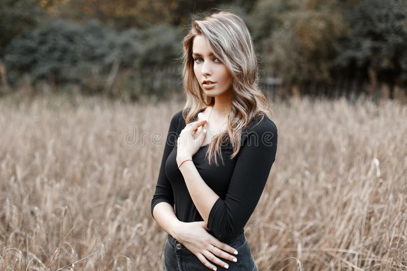 Beautiful pretty sexy young woman in a black stylish T-shirt with blond hair in trendy jeans poses in a field on a warm autumn day. Modern cute girl model stock image