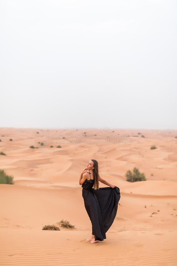 Beautiful pretty woman in black dress on a sand dune of desert stock photography