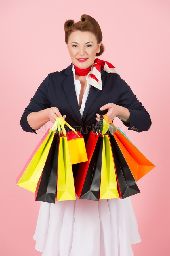 Beautiful woman in jacket with colored shopping paper bags over rose pink background. Charming beautiful brunette shopping time stock image
