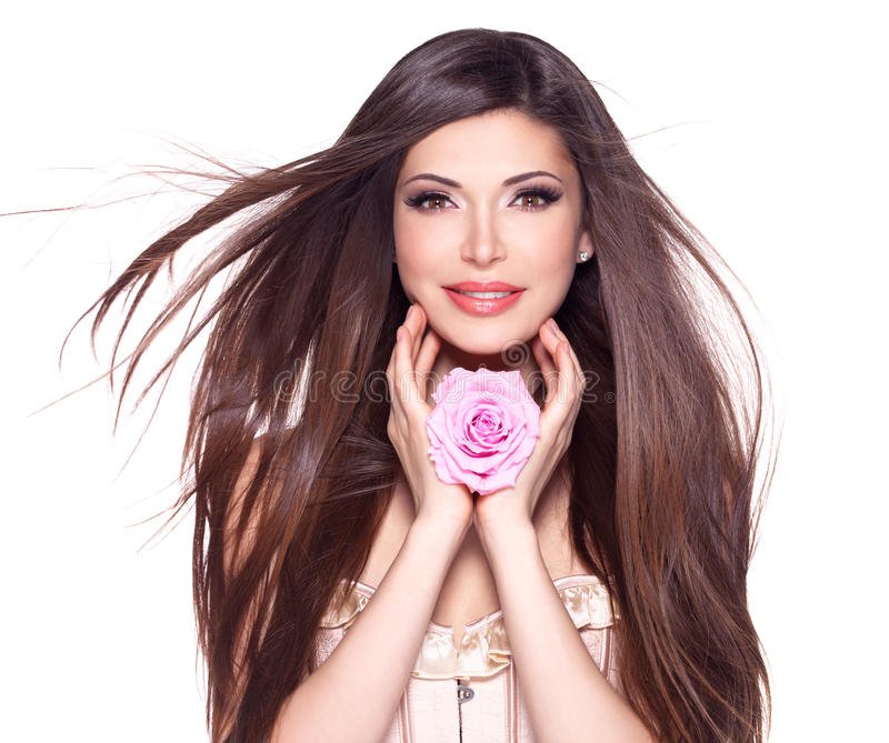 Beautiful pretty woman with long hair and pink rose at face. Portrait of a beautiful white pretty woman with long straight hair and pink rose at face stock photo