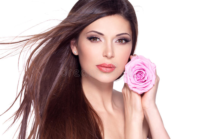 Beautiful pretty woman with long hair and pink rose at face. royalty free stock photography
