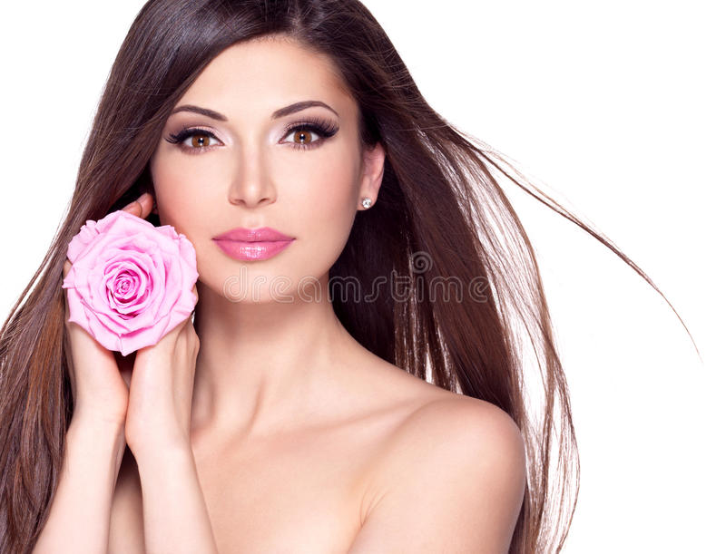 Beautiful pretty woman with long hair and pink rose at face. Portrait of a beautiful white pretty woman with long straight hair and pink rose at face royalty free stock photo