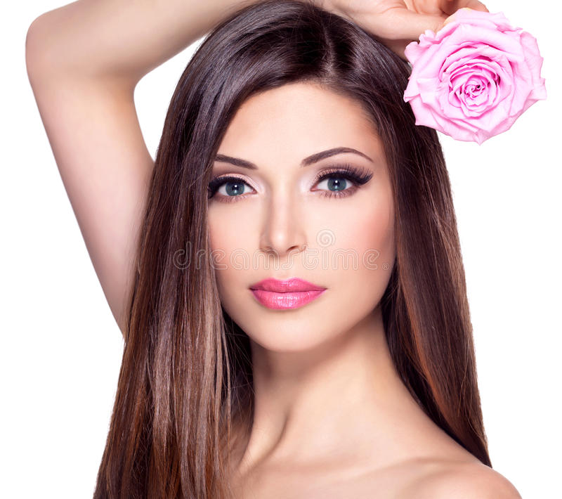Beautiful pretty woman with long hair and pink rose at face. Portrait of a beautiful white pretty woman with long straight hair and pink rose at face stock image