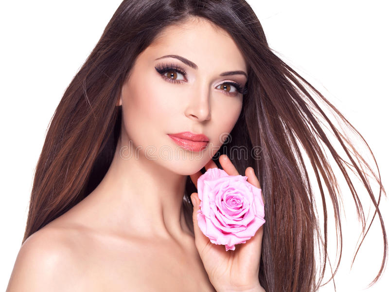 Beautiful pretty woman with long hair and pink rose at face. Portrait of a beautiful white pretty woman with long straight hair and pink rose at face stock photography
