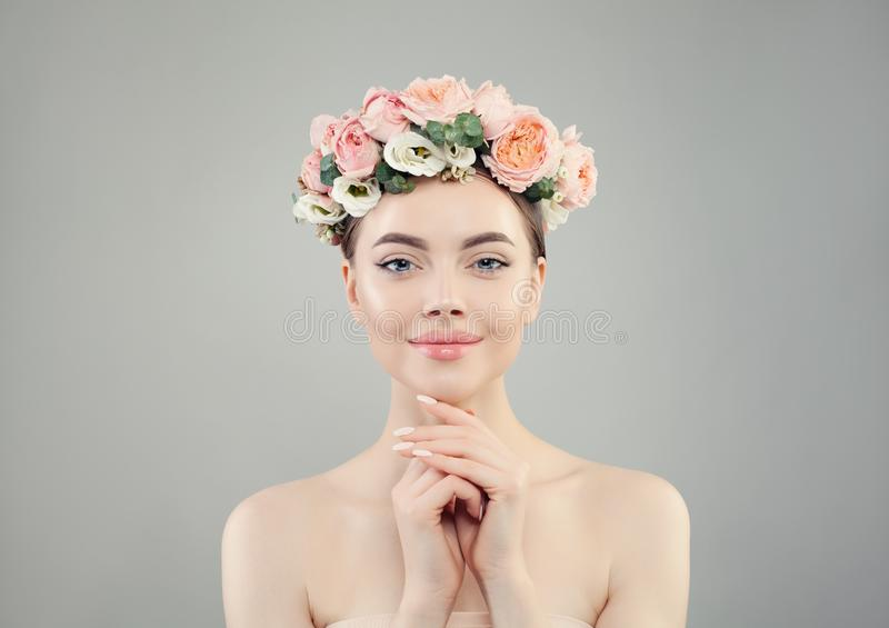 Beautiful pretty woman in rose flowers crown portrait. Healthy spa model with clear skin and manicured nails stock images