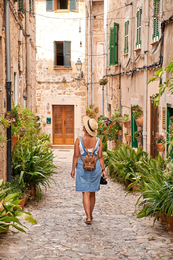 Beautiful pretty woman walking at old town pavement street with flowers and looking away. Travel concept royalty free stock photography