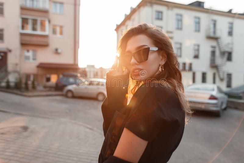 Beautiful pretty young hipster woman in trendy clothes in retro style in fashionable dark sunglasses is posing outdoors. In the city on a sunny spring warm day royalty free stock image