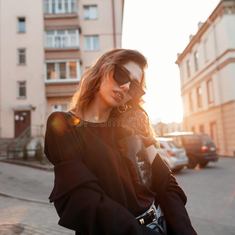 Beautiful pretty young hipster woman in trendy clothes in retro style in fashionable dark sunglasses is posing outdoors. In the city on a sunny spring warm day royalty free stock images