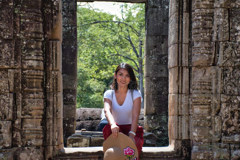 Beautiful, pretty, young Thai girl is exploring the ancient ruins of Angkor Wat City/Capital of Temples Hindu temple complex in. Siem Reap, Cambodia. The stock photos