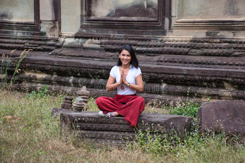 Beautiful, pretty, young Thai girl is exploring the ancient ruins of Angkor Wat City/Capital of Temples Hindu temple complex in. Siem Reap, Cambodia. The royalty free stock images