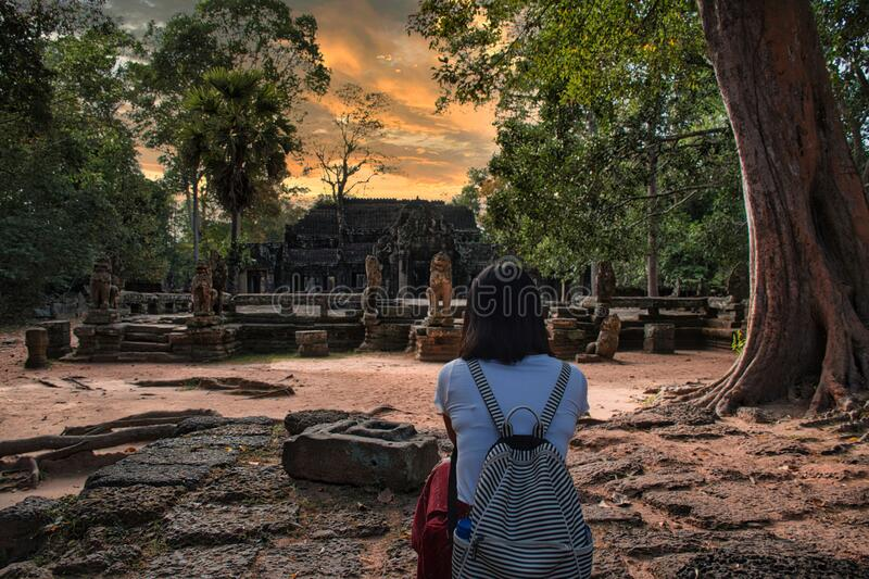 Beautiful, pretty, young Thai girl is exploring the ancient ruins of Angkor Wat City/Capital of Temples Hindu temple complex in. Siem Reap, Cambodia. The royalty free stock photography