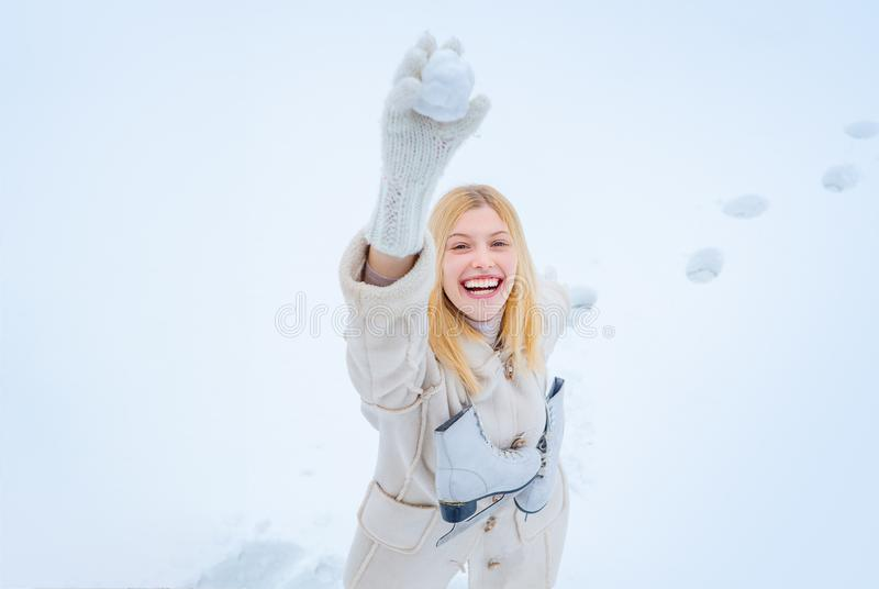 Beautiful pretty young woman in winter. Young blond woman in sweater and funny hat holding white skates over shoulder in stock images