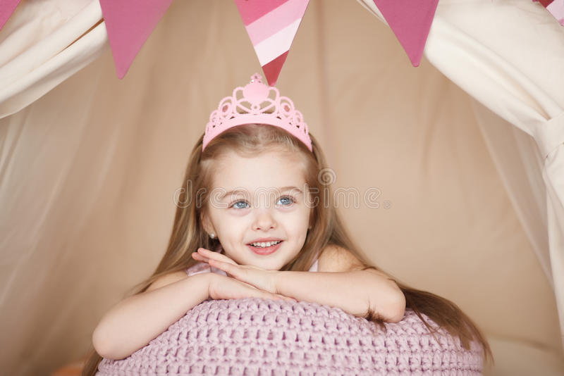 Beautiful princess girl in pink dress lying down bored. royalty free stock photography