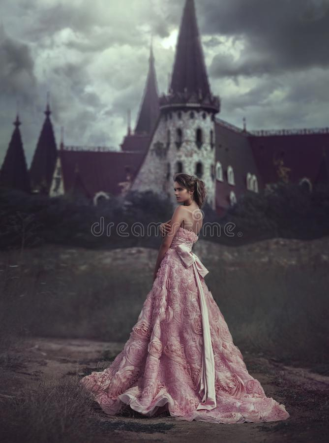 Beautiful Princess in pink dress on the background of majestic castle. blonde with long hair is on the way to the castle stock images