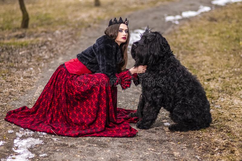 Beautiful Princess in Red Dress And Black Fur with Crown and Her Dog in Forest During Early Spring. Art Photography royalty free stock image