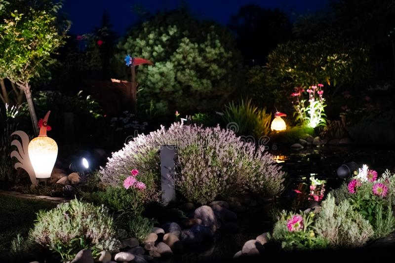 Beautiful private garden on summer night lightened by illuminated artistic glass birds stock photos