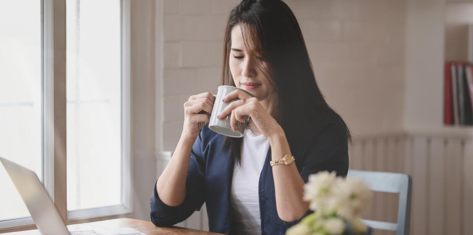 Beautiful professional businesswoman drinking a cup of coffee while working on her project stock photography