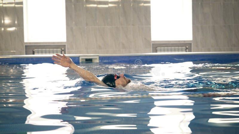 Beautiful professional swimmer swiming backstroke in the pool, camera dolly shot. Beautiful bearded professional swimmer swiming backstroke in the pool, e view stock photos