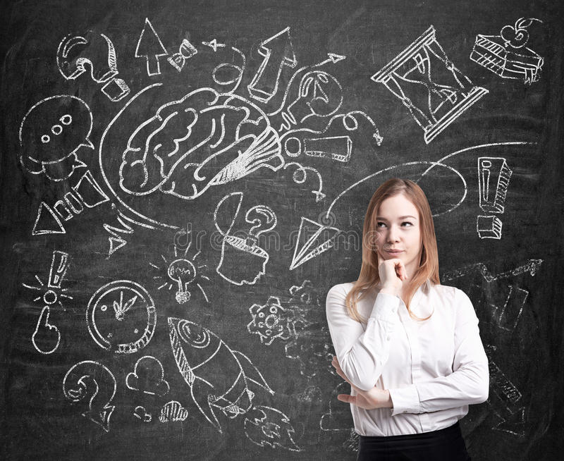 A beautiful professional is thinking about business development. A business development sketch is drawn on the black chalkbo stock photo