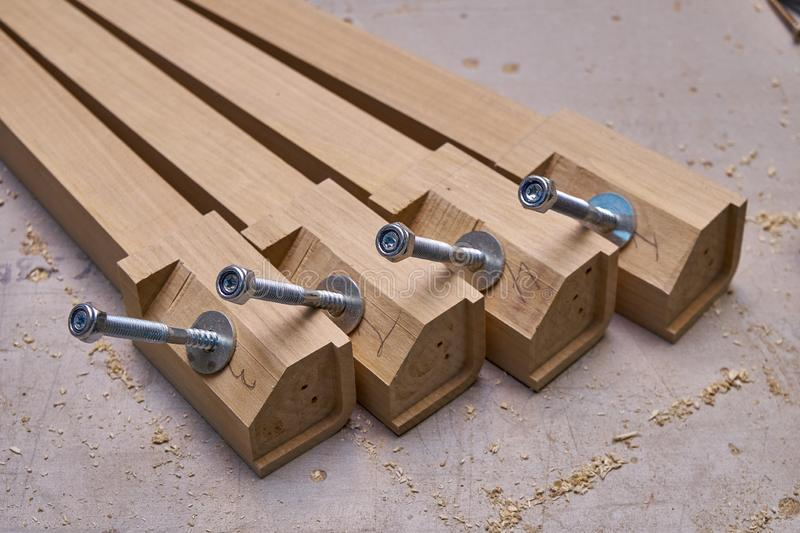 Solid wood table legs building process. Wooden furniture manufacturing process. Furniture manufacture. Close-up. Beautiful professionally made solid wood table stock photography