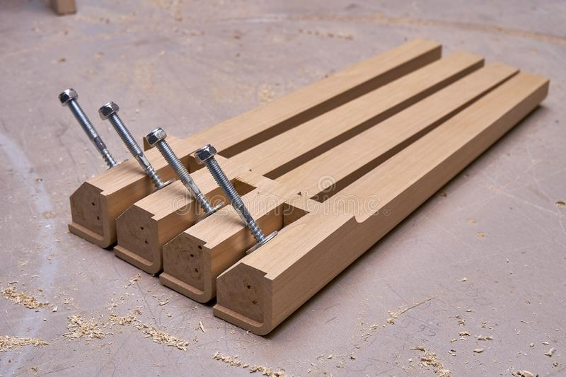 Solid wood table legs building process. Wooden furniture manufacturing process. Furniture manufacture. Close-up. Beautiful professionally made solid wood table royalty free stock images