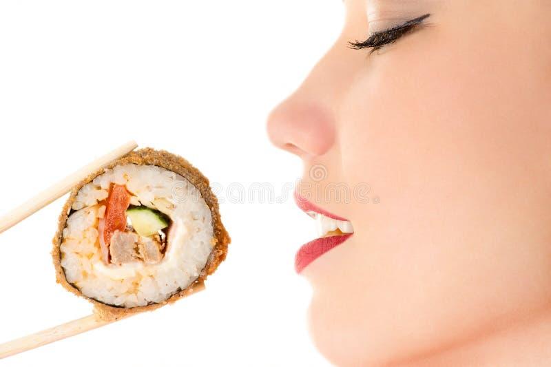 Beautiful profile face girl eating sushi roll closeup stock photography